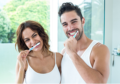 man-and-woman-brushing-their-teeth