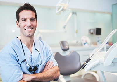 smiling-male-dentist-in-exam-room